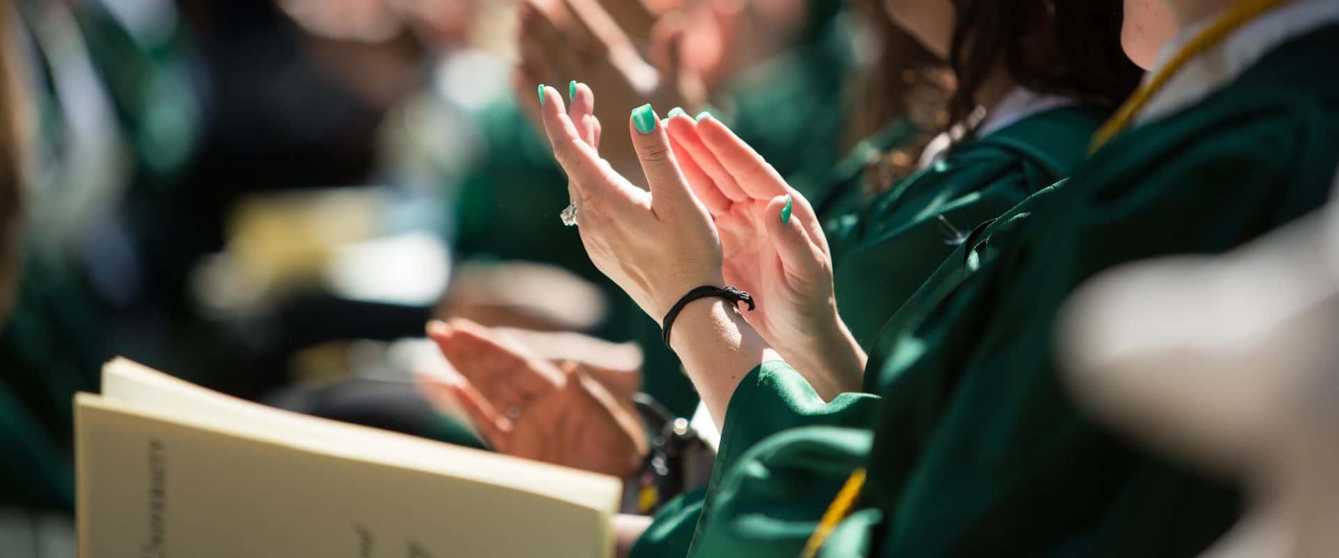 A student claps at graduation
