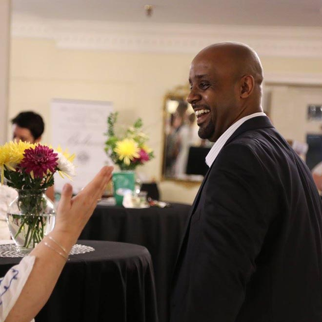WPU alumni smiling at a networking event.