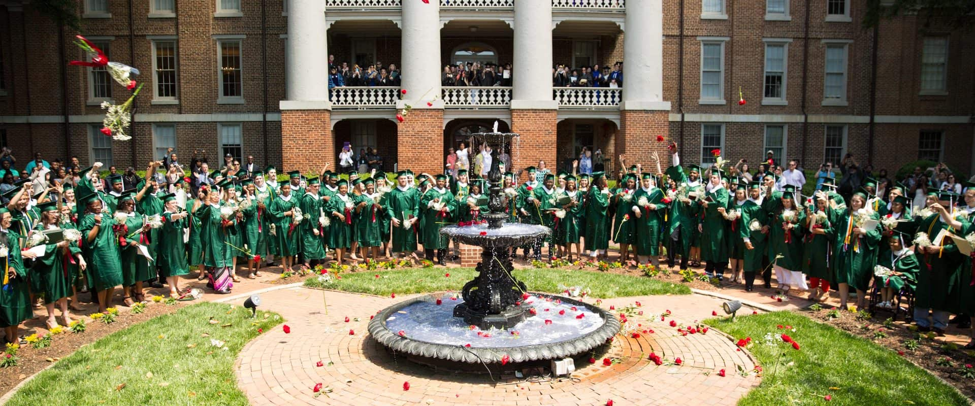 Graduates toss their roses into Main fountain.
