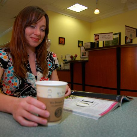 A student drinking coffee in Peace Perk coffee shop.