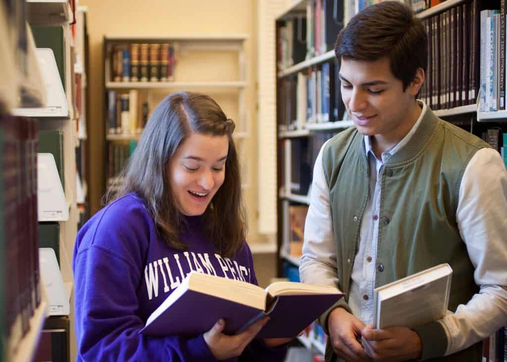 WPU students reading a book.