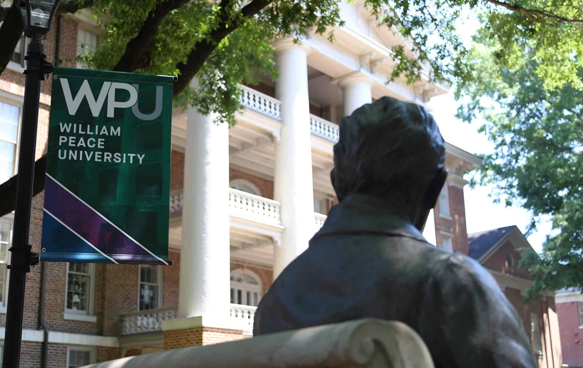Mr. Peace and Main Building with a WPU banner.